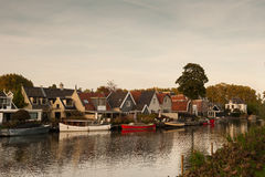 Small river  De Vecht. Houses and boats on the shore of the small river De Vecht in Utrecht, Holland with stripes of aeroplanes Stock Image