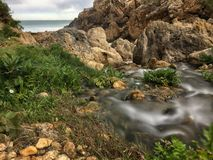 Small river empties into the sea. Between rocks in an unpopulated environment. Asturias, Spain royalty free stock photo