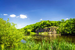 Small river and hills by summertime. Royalty Free Stock Photo