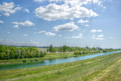 Small River Lined with Trees and Blue Sky with White Clouds Abov. River Lined with Trees and Greenfields and Blue Sky Above Royalty Free Stock Photos