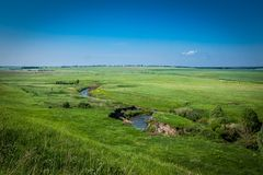 A small river, meandering, flows across a green plain. stock photos