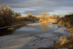 Small river partially frozen at sunset royalty free stock image