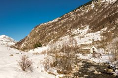Small river and snowy mountain in the Pyrenees in winter Royalty Free Stock Photography