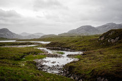 Small river streaming through the peat landscape. River flowing downstream to the sea through the peat meadows. Grey sky and clouds Royalty Free Stock Photo