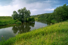 A small river and trees along it. A small river in the village and trees growing on the banks Stock Photos