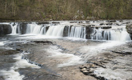 Small river waterfall in rural setting. Motion blur of small river waterfall in english countryside rural setting Royalty Free Stock Photo