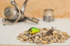 Small roach and a metal spoon lying on a hill of pebbles, the instantaneous coil in the background. Items for fishing. 11/05/2016 Stock Photography