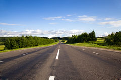 Small road. The asphalted road passing through fields and woods (in countryside Royalty Free Stock Photography