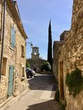Small street in the south of France. Small road leading to the church square in an authentic village of the south of France near Uzès in the Gard. The yellow Royalty Free Stock Photo