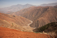 Small road placed between mountains of brown sand and dirt. Small road placed between mountains of brown sand and dirt to travel from one side of the mountain Royalty Free Stock Photography