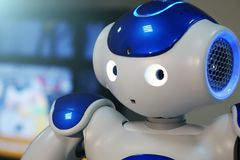 A small robot with a human face and a humanoid body. Artificial intelligence - AI. Blue-and-white robot. A small robot with a human face and a humanoid body royalty free stock photography