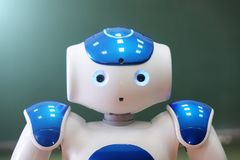 A small robot with a human face and a humanoid body. Blue-and-white robot. A small robot with a human face and a humanoid body. Artificial intelligence - AI stock images