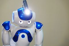 A small robot with a human face and a humanoid body. Artificial intelligence - AI. Blue-and-white robot. A small robot with a human face and a humanoid body royalty free stock photos