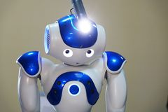 A small robot with a human face and a humanoid body. Artificial intelligence - AI. Blue-and-white robot. A small robot with a human face and a humanoid body royalty free stock image
