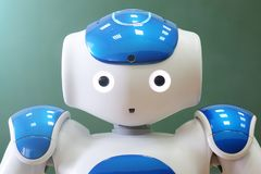 A small robot with a human face and a humanoid body. Blue-and-white robot. A small robot with a human face and a humanoid body. Artificial intelligence - AI royalty free stock photos