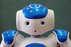 A small robot with a human face and a humanoid body. Blue-and-white robot. A small robot with a human face and a humanoid body. Artificial intelligence - AI royalty free stock photography