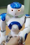 A small robot with a human face and a humanoid body. Blue-and-white robot. A small robot with a human face and a humanoid body. Artificial intelligence - AI royalty free stock image