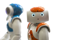 Small robots with human face and body. AI. Small robots with human face and body - humanoid. Artificial Intelligence - AI. Orange and blue robots isolated on Stock Image