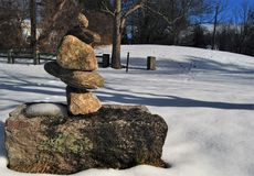 A small rock arrangment in a snow covered field on a bright mid winter day. Barren trees, blue skies, fence, moss covered rock stock images