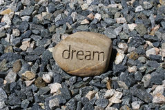Small rock big dream. A big dream rock stands out among smaller stones, a rock with the word dream inscribed in it Royalty Free Stock Image