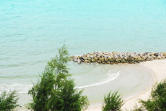 Small rock dam with beautiful tropical beach behind pine tree Stock Photo