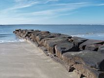 Sullivan`s Island, South Carolina. A small rock jetty enters the water on Sullivan`s Island, South Carolina stock photography