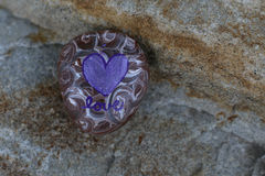 Small rock painted white and purple swirls with purple heart. On a colorful boulder is a small painted rock.  Purple and white swirls and a purple heart are Stock Photos