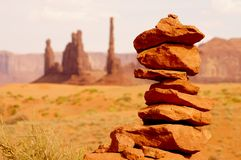 Small rock tower in front of impressive desert landscape. Rocks balanced on each other with view on a hot american national park Royalty Free Stock Photo