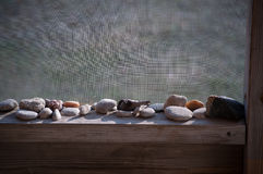 Small rocks on a wooden ledge shelf Stock Images