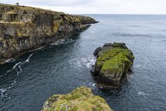 Small rocky island covered by green moss