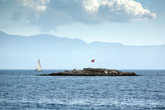 A small rocky island with a flag of Turkey. In addition to sailing boat floats. Blue cruise on Stock Photos