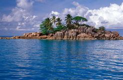 Small rocky island with palm trees. St. Pierre rocky island near the North coast of Praslin, Seychelles stock image