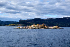 Small rocky island with small trees Stock Images