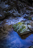 Small rocky stream with reflections of blue Stock Photos