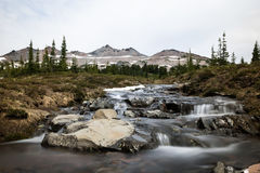 Small rocky stream under distant alpine peaks of Washignton. Small rocky stream runs through a meadow below large rocky peaks in the Gifford Pinchot National Royalty Free Stock Photo