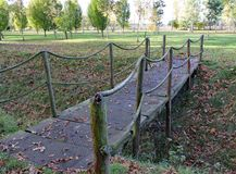 A small rope bridge crosses a ditch at Arley Arboretum in the Midlands in England stock photography