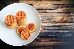 Round waffles in a white plate on a brown wooden background royalty free stock photo