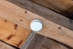 Small round battery operated device to warn residents of fire. In an old wooden house Stock Photography