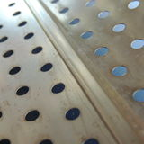 Small round holes in a thin metal sheet Stock Image