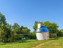 Small round house with blue domed roof on green lawn on day Stock Image