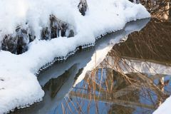 Small round icicles over water. Perfect reflection Stock Photography