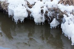 Small round icicles over water. Perfect reflection Royalty Free Stock Images