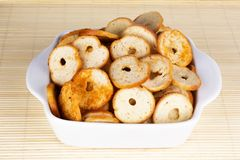 Small round mini bake rolls in a white bowl. Small round mini bake rolls with a hole inside in a white bowl Stock Image