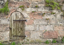Small round wooden door in an old masonry Stock Images