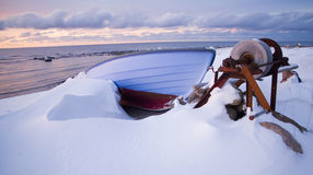 Small row boat laying on a pebble beach covered in snow Royalty Free Stock Image