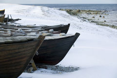 Small row boat laying on a pebble beach covered in snow Stock Photo