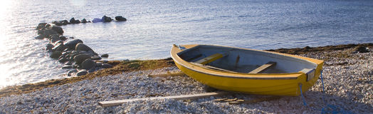 Small row boat laying on a pebble beach Stock Images