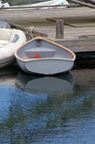 Small Row Boat Reflection. A small gray wood row boat tied to a wooden dock floating on the water with a reflection Stock Image