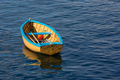 A small row boat sitting calmly in a harbor Royalty Free Stock Photo