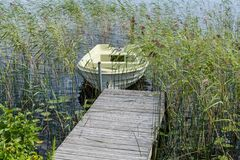 Small row boat tied to a pier surrounded by green sea weed Royalty Free Stock Photos